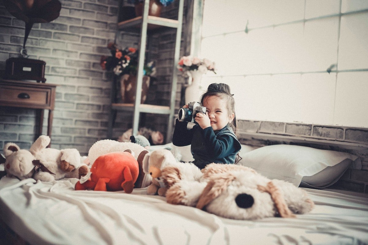 A Baby Surrounded by Stuffed Animals Plays With a Toy Camera on a Bed Salsify Toy and Baby Brand PXM