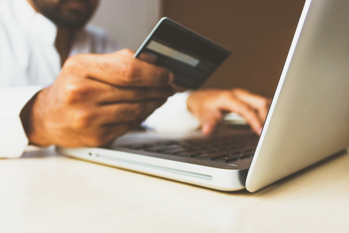Man Holds Credit Card as He Shops Online Salsify D2C Apparel Brand Challenges