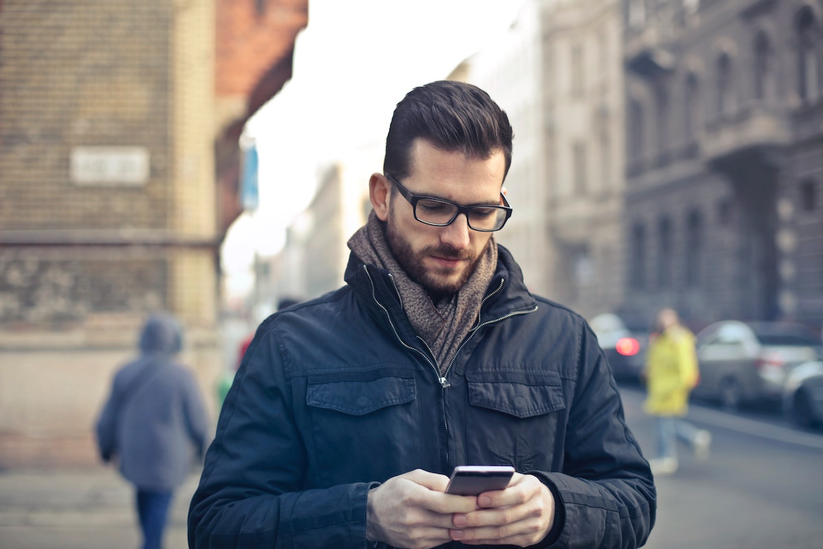 Man Wearing Black Jacket Looks at His Phone on a City Street Salsify Ecommerce Trends 2020