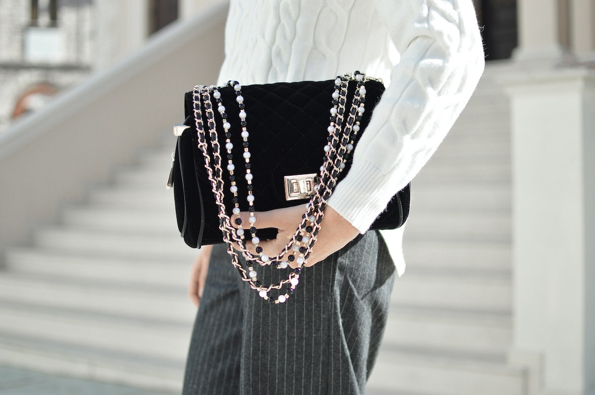 Woman%20Holds%20a%20Designer%20Purse%20While%20Standing%20in%20Front%20of%20a%20White%20Building%20Salsify%20Brands%20and%20Marketplaces